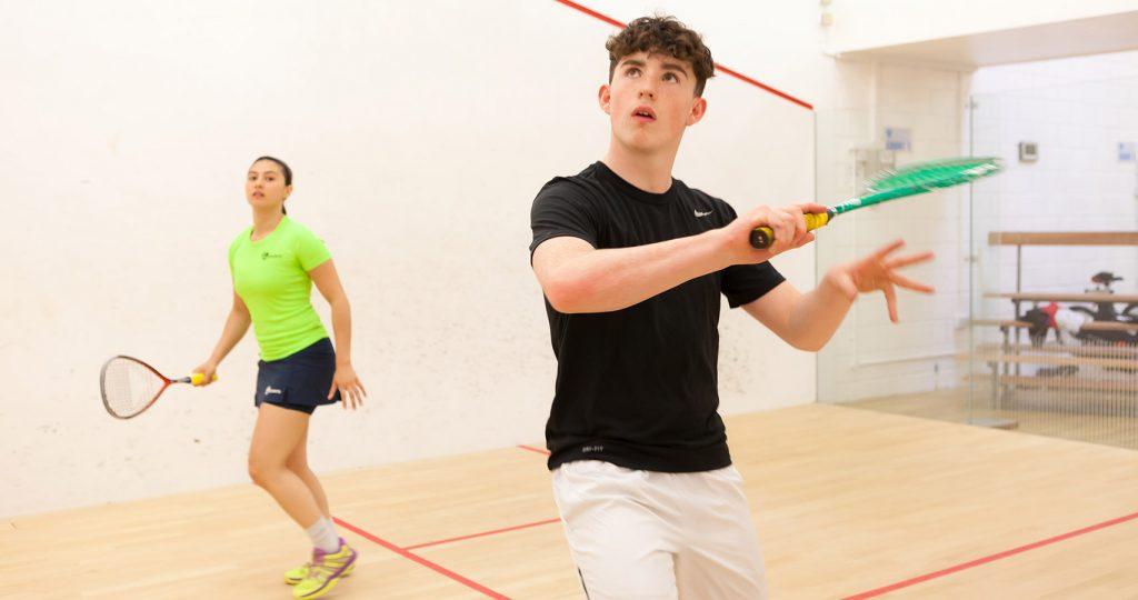 um homem jovem e um a mulher jogando squash